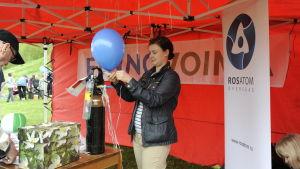 Kvinna står i Fennovoimas tält på Parhalahtidagen och blåser upp ballonger