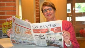 Marina Holmberg med tidningen Västra Nyland i händerna.