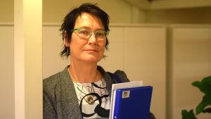 En kvinna med kort mörkt hår och gröna glasögonbågar håller i en bunt papper. Hon heter Kukka-Maaria Luukkonen.