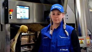 Mjölkbonden Sofia Eriksson står framför mjölkroboten.