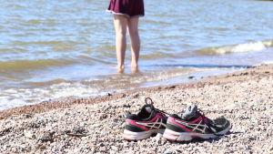 Flicka som står på stranden.