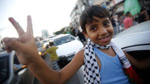 Palestinsk pojke visar segertecken under firandet av eldupphöret i Gaza.