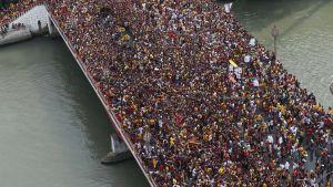 Filippinska katoliker i procession över bro i Manila under firandet av kristusstatyn Black Nazarene, 9.1.2016