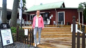 Kvinna står på en terass framför en restaurang som är av rödmålat trä och med grönt tak