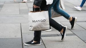 En hand som håller en papperspåse från klädbutiken Mango.
