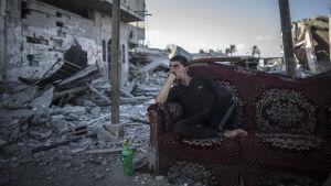 Palestinier sitter utan för sitt förstörda hem i östra Gaza City.