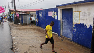 A Liberian man walks past the M V Massaquoi Elementary school in West Point where Ebola patients fled following an attack and looting by protesters in Monrovia.