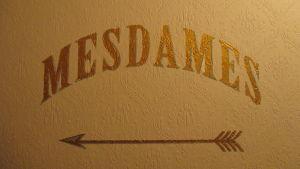 Seinään maalattu ranskankielinen teksti mesdames ja nuoli, jotka ohjaavat naistenhuoneeseen