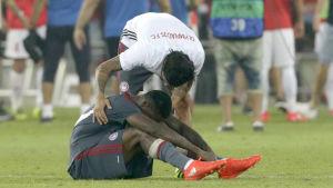 En Olympiakos-spelare tröstar en annan.