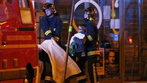 Skadade evakueras utanför konserthuset Bataclan.