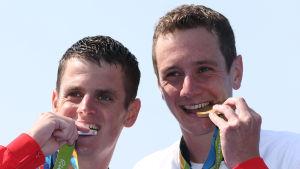 Bröderna Jonathan och Alistair Brownlee biter i sina OS-medaljer.