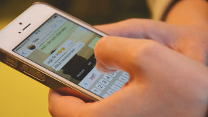 En närbild av händer som skriver meddelandet vgd på appen whatsapp på en smarttelefon.