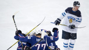 En besviken finsk ishockeyspelare med jublande franska spelare i förgrunden.
