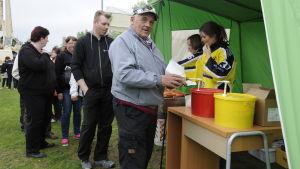 Korvförsäljning  på Parhalahtidagen i Pyhäjoki, man med korv i handen