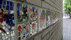 Remsa av mosaik på en gammal tegelvägg.