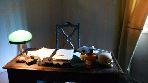 Gammalt skrivbord med lampa, apoteksflaskor, anteckningar, bläckpenna.