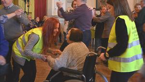 Närvårdarstuderande dansar med dam i rullstol