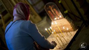 Nainen sytyttää tuohuksen ortodoksikirkossa