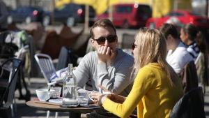 Vänner dricker kaffe ute på terrass.