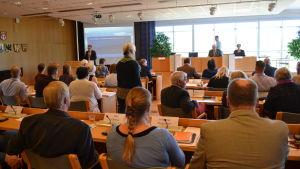 Ryggar på fullmäktigeledamöter under möte i Pargas stadsfullmäktige.