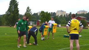 rugbyspelare på gräsplan håller upp gula dynor