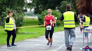 Funktionärer visar vartåt en triathlet ska springa. På bilden finns också bord med vattenmuggar åt triatleterna.