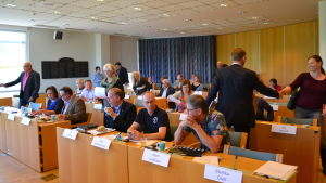 Ledamöter i Pargas stadsfullmäktige skakar hand inför mötet.