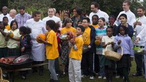 Michelle Obama skördar grönsaker i Vita Husets trädgård tillsammans med skolbarn.