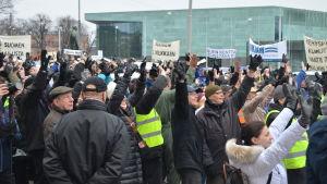 Hundratals demonstranter vinkar till en nyhetshelikopter som flyger ovanför.