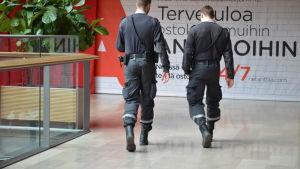 Två ordningsvakter i ett köpcentrum.
