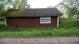 Skylt på rött uthus i Hanhikivi by, tassarna bort från Hanhikivi