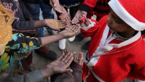 En liten indisk pojke delar ut godis i slummen i staden Amritsar den 25 december.