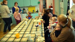 Mammor och barn äter vid Pernå församlings klubb i prästgården.