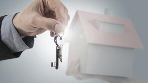 Temabild: En manshand håller i en nyckelknippa medan en kvinnohand håller upp ett miniatyrhus i bakgrunden.