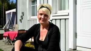Pernilla Vikström sitter i solen på trappan till hennes hem
