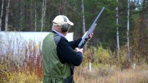 Jägaren och skytten Henrik Gullans står på Eidets skjutbana med ryggen mot kameran. I händerna håller han ett halvautomat gevär och på huvudet har han hörselskydd.