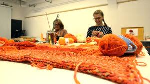 Hannele Palm och Veronica Lönnqvist sitter och stickar i ett klassrum. Framför dem ligger mängder av garn i olika orange nyanser.