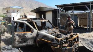 En afghansk polis inspekterar en polisbil som tänts eld på under en attack mot en vägspärr i nordöstra Afghanistan.