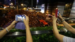 Folk videofilmar protesterna i Hongkong 2014