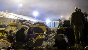 Flyktingar sover utomhus vid gränsen mellan Österrike och Slovenien.