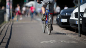Anonyymi mies pyöräilee pyöräkaistalla kaupungissa kesällä.