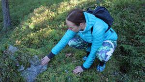 Nainen tunnustelee kiveä ja sammalta