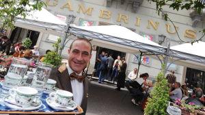 Hymyilevä miestarjoilija kantaa tarjotinta kuppeineen kahvilan edessä.