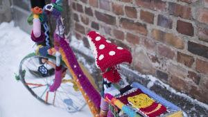 En cykel som dekorerats med olika virkade arbeten i granna färger.