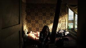 Ivans rival i borgmästarvalet sitter och röker på sängen i sitt minimala sovrum.