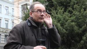 Jan kuuntelee linnunääntä käsi korvallaan.