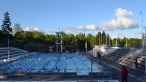 Vy över Samppalinna utebad, folk simmar i bassängen en sommarmorgon.