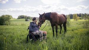 Nicole Hellberg sitter i sin rullstol ute i hagen med sin häst.