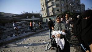 Palestinier vid ett sönderbombat hus i Gaza City den 21 juli.
