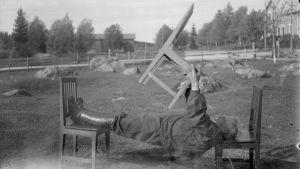"""En man leker """"ligga lik"""", där man ska hålla sin kropp så styv att man kan ligga raklång mellan två stolar och lyfta en tredje stol. Bilden är tagen 1931 i Närpes, Kalaks."""